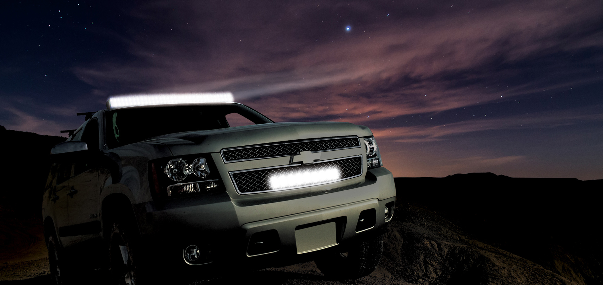 Cyclops LED Bar Light shining into the night sky attached above SUV windshield